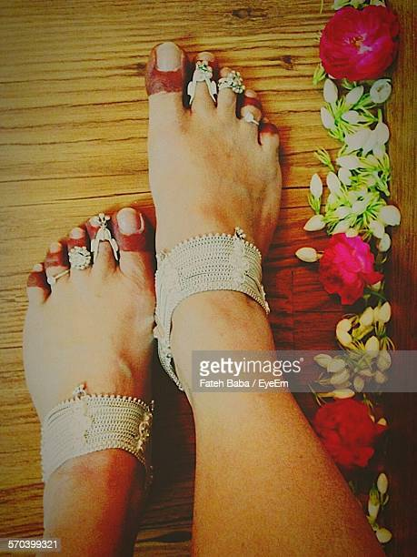 Low Section Of Woman Feet With Anklets And Toe Rings On Wood