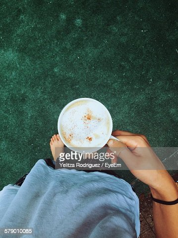 Low Section Of Woman Holding Coffee While Standing Outdoors