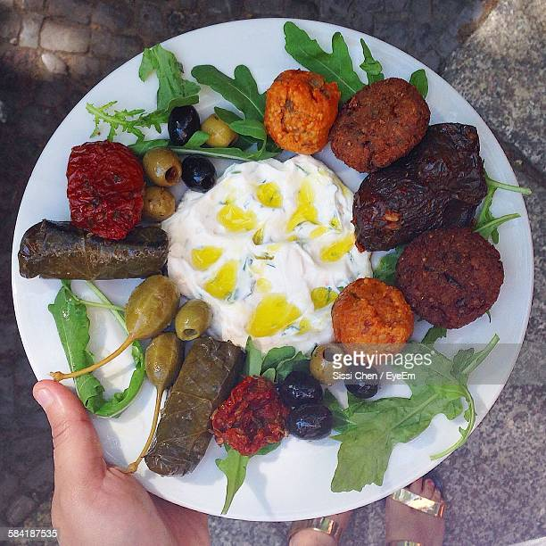Low Section Of Woman Holding Falafel With Vegetables In Plate