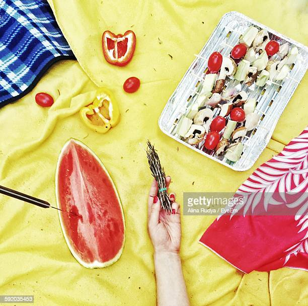 Low Section Of Woman Holding Herb With Fruits And Vegetables On Picnic Blanket