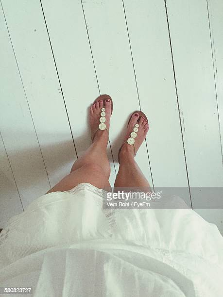 Low Section Of Woman In White Dress Standing On Hardwood Floor