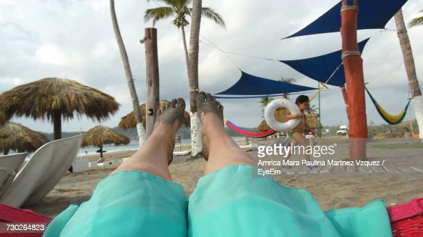 Low Section Of Woman Lying In Hammock While Boy Walking With Inflatable Ring At Beach