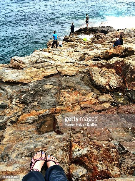 Low Section Of Woman On Rock Formation Against People Fishing In Sea