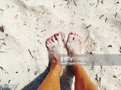 Low Section Of Woman On Sand During Sunny Day