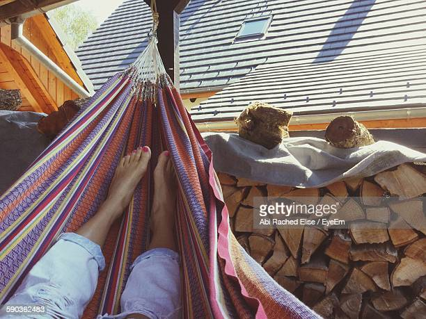 Low Section Of Woman Relaxing In Hammock Against House
