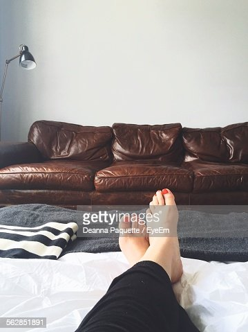 Low Section Of Woman Relaxing In Living Room