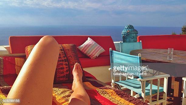 Low Section Of Woman Relaxing On Sofa Against Sea