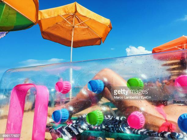 Low Section Of Woman Resting At Beach Seen Through Inflatable During Sunny Day