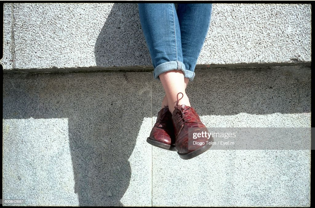 Low Section Of Woman Sitting On Retaining Wall