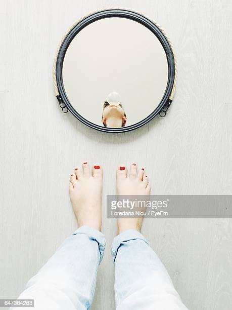 Low Section Of Woman Standing Against Mirror With Reflection On Floor