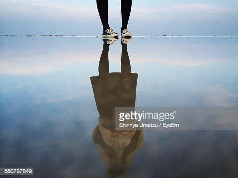 Low Section Of Woman Standing By Her Reflection Of Lake