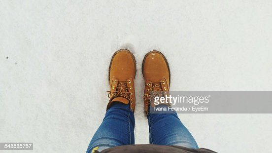 Low Section Of Woman Standing In Snow