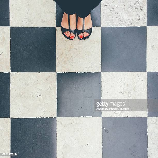 Low Section Of Woman Standing On Checked Flooring