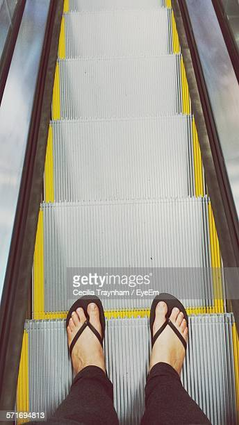 Low section of woman standing on escalator in building