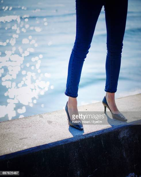 Low Section Of Woman Standing On Retaining Wall Against Sea