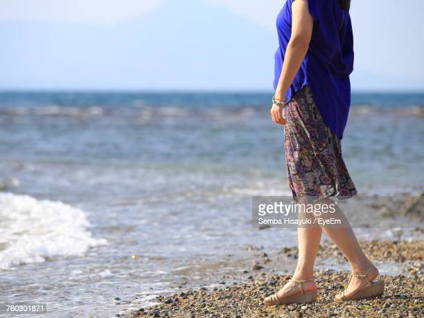 Low Section Of Woman Standing On Shore At Beach