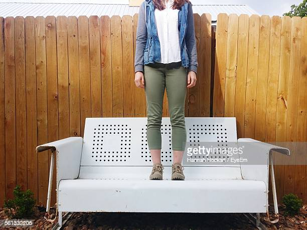 Low Section Of Woman Standing On Sofa Against Fence In Backyard