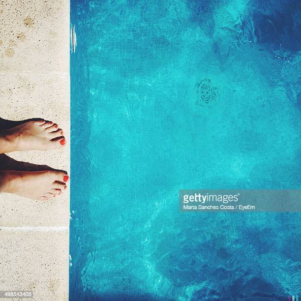 Low section of woman standing poolside