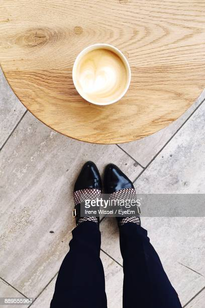 Low Section Of Woman Standing With Coffee On Table