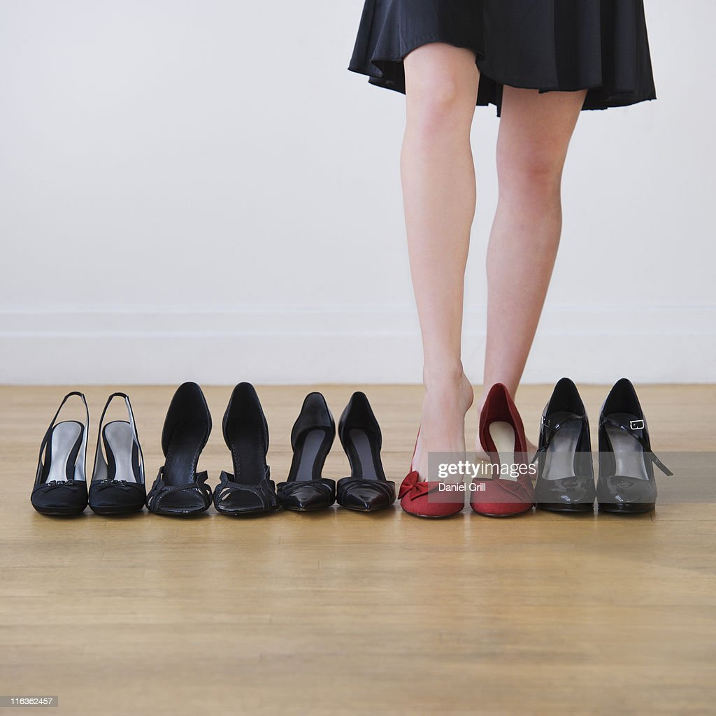 Low section of woman trying on shoes