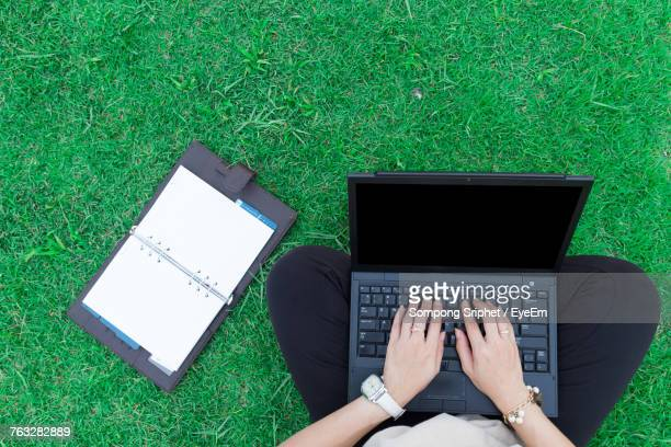 Low Section Of Woman Using Laptop On Field