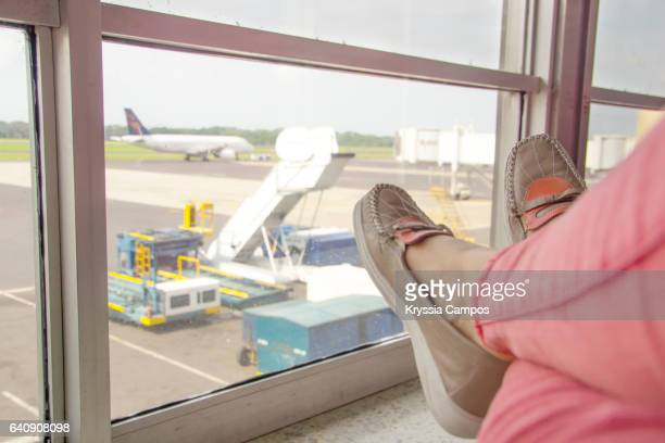 Low section of woman waiting for flight at the airport lounge