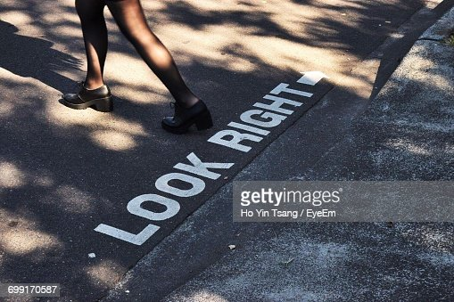 Low Section Of Woman Walking By Markings On Road