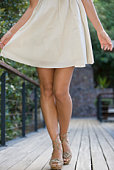 Low section of woman walking is heels and a summer dress