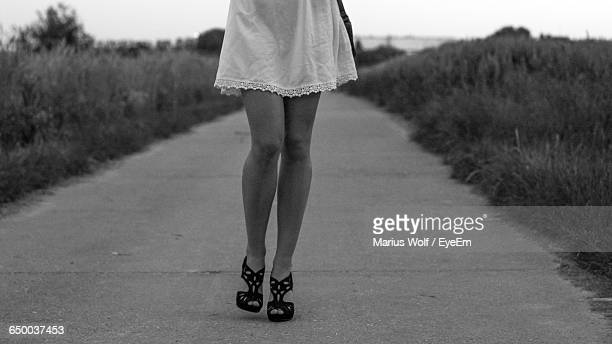 Low Section Of Woman Walking On Road Amidst Grass