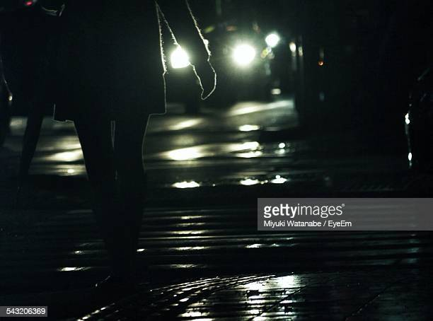 Low Section Of Woman Walking On Sidewalk At Night