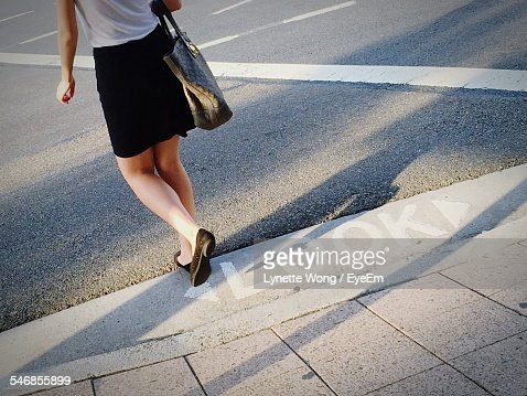 Low Section Of Woman Walking On Street