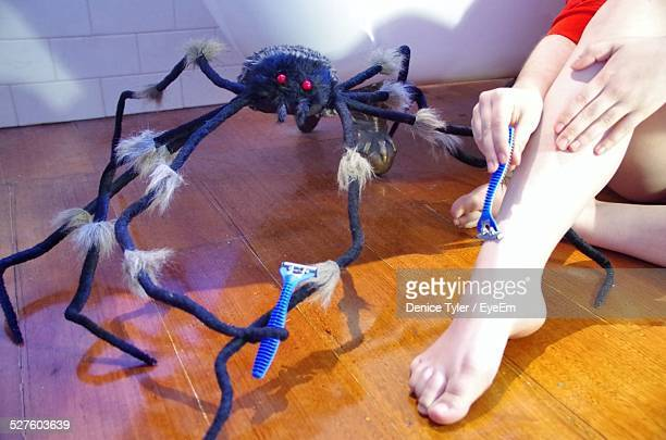 Low Section Of Woman Waxing With Razor Against Toy Spider At Home