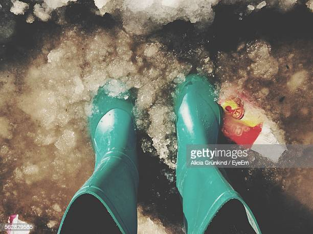 Low Section Of Woman Wearing Green Rain Boots Standing In Snow