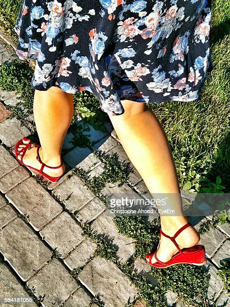 Low Section Of Woman Wearing Red Sandal Walking On Cobblestone Street