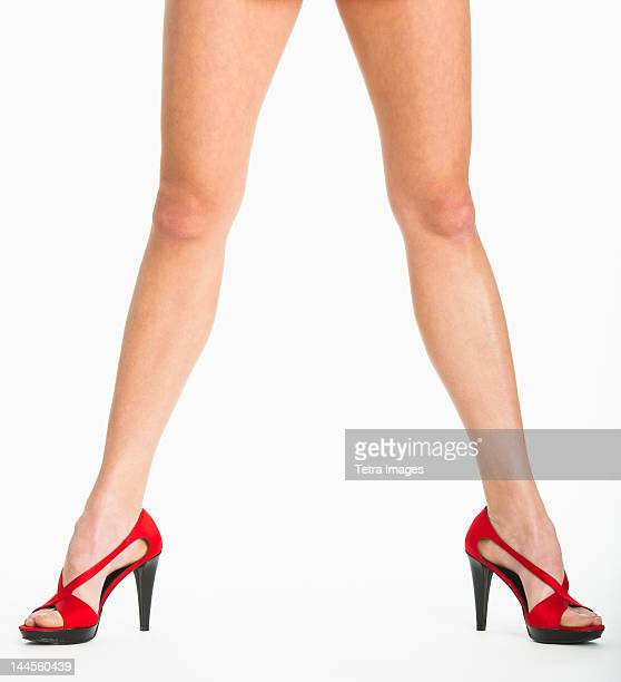 Low section of woman wearing red shoes on white background