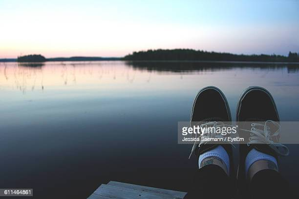 Low Section Of Woman Wearing Shoes Over Lake Against Sky During Sunset