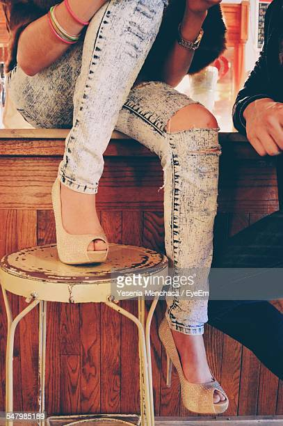 Low Section Of Woman Wearing Torn Jeans And Stiletto Sitting On Bar Counter
