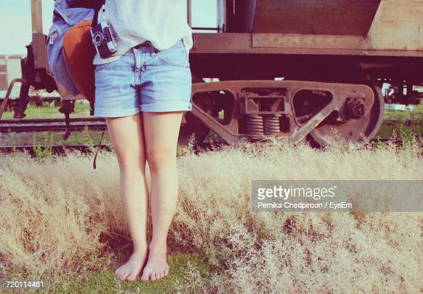 Low Section Of Woman With Bag Standing By Old Train On Grassy Field