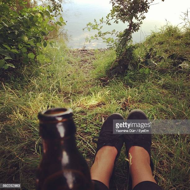 Low Section Of Woman With Bottle Relaxing On Cliff