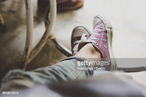 Low Section Of Woman With Crossed Legs In Purple Shoes