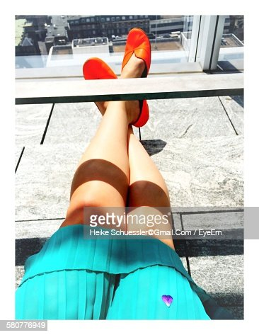 Low Section Of Woman With Legs Crossed By Railing