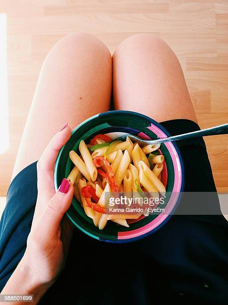 Low Section Of Woman With Pasta On Lap At Home