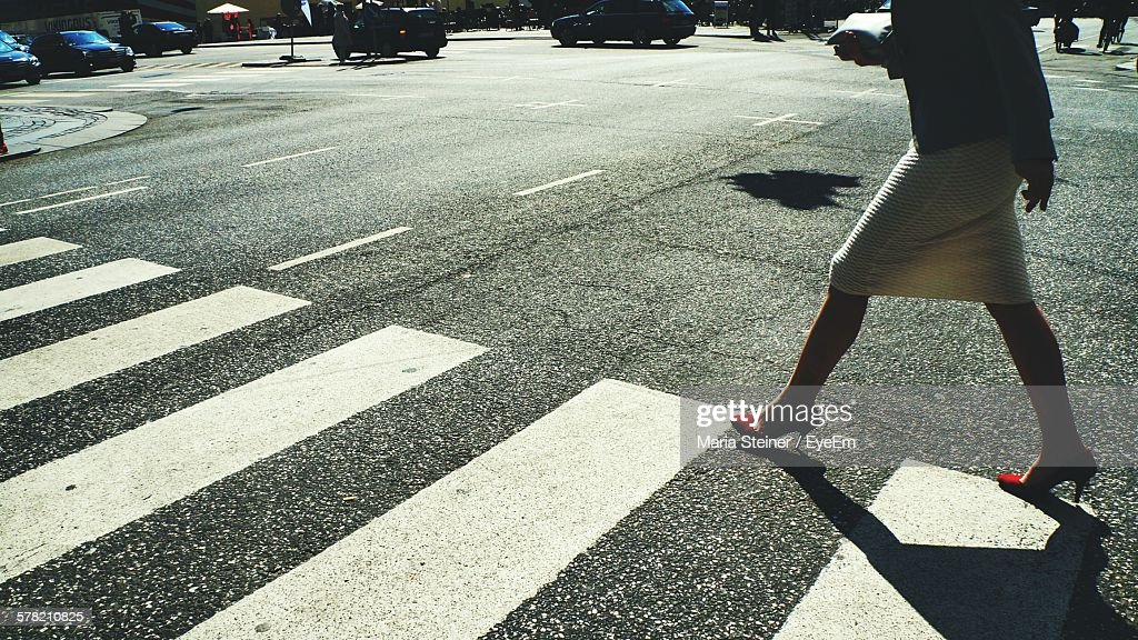 Low Section Of Woman With Red High Heels Crossing City Street