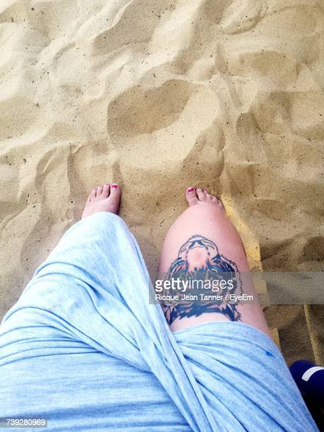 Low Section Of Woman With Tiger Tattoo While Relaxing At Beach
