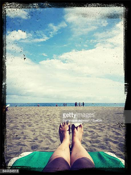 Low Section Of Woman With Wounded Leg On Beach Against Cloudy Sky