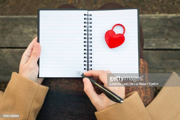 Low Section Of Woman Writing In Spiral Notebook