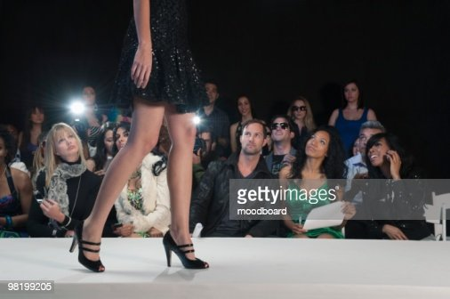 Low section of womans walking in black high heeled shoes on fashion catwalk : Stock Photo