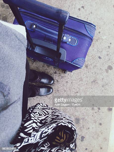 Low Section Of Women Dressed Neatly Standing By Luggage On Vacation