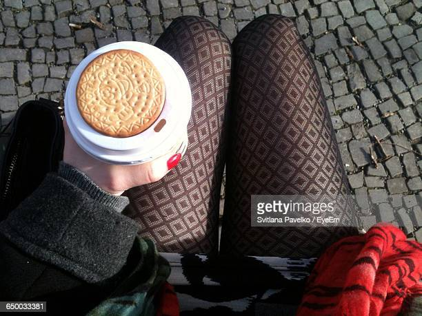 Low Section Of Women Holding Disposable Coffee Cup Along With Biscuit