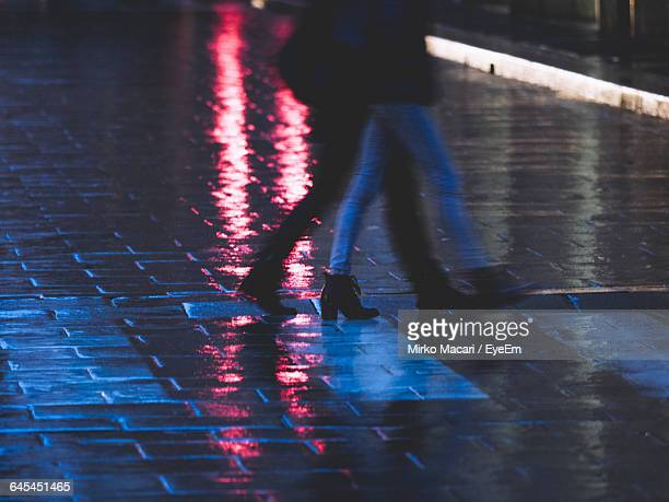 Low Section Of Women Walking On Wet Street During Monsoon
